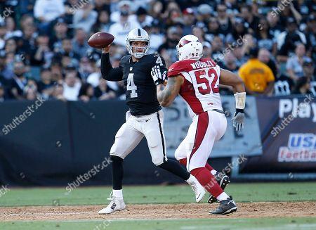 Derek Carr, LaMarr Woodley. Oakland Raiders quarterback Derek Carr (4) passes as Arizona Cardinals linebacker LaMarr Woodley (52) applies pressure during the first half of an NFL preseason football game in Oakland, Calif