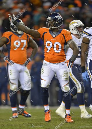 Denver Broncos defensive end Shaun Phillips (90) motions to teammates against the San Diego Chargers in the fourth quarter of an NFL AFC division playoff football game, in Denver