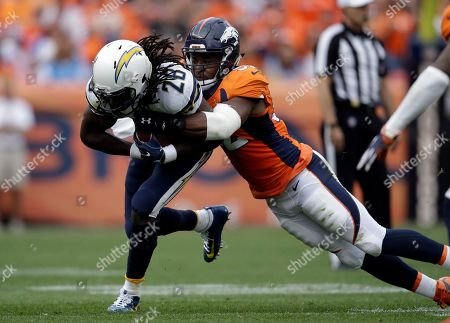 Corey Nelson, Melvin Gordon. San Diego Chargers running back Melvin Gordon (28) is tackled by Denver Broncos outside linebacker Corey Nelson (52) during an NFL football game between the Denver Broncos and the San Diego Chargers, in Denver
