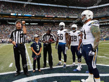 Referee Peter Morelli flips the coin as San Diego Chargers' Donald Butler (56), Marcus Gilchrist (38) and Nick Hardwick (61) look on before a preseason NFL football game against the Seattle Seahawks, in Seattle