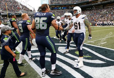 Seattle Seahawks' Zach Miller (86) shakes hands with San Diego Chargers' Nick Hardwick (61) before the coin flip before a preseason NFL football game, in Seattle
