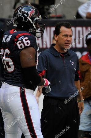 Houston Texans coach Gray Kubiak shakes Houston Texans offensive tackle Ephraim Salaam (66) hand before the start of the Houston Texans game in an NFL football game, in Houston