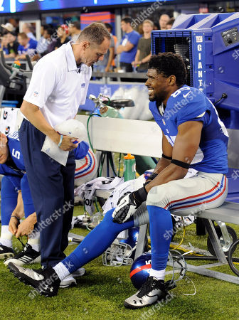 A trainer works on New York Giants wide receiver Ramses Barden, right, during the second half of an NFL preseason football game against the Indianapolis Colts, in East Rutherford, N.J