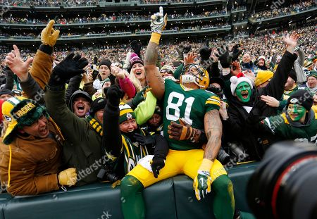 Green Bay Packers tight end Andrew Quarless celebrates a touchdown with fans during the first half of an NFL divisional playoff football game against the Dallas Cowboys, in Green Bay, Wis