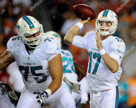 Nate Garner, Ryan Tannehill. Miami Dolphins quarterback Ryan Tannehill (17) throws a pass against the Tampa Bay Buccaneers during the first quarter of an NFL football game, in Tampa, Fla. Blocking is Dolphins' Nate Garner (75