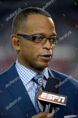 ESPN commentator Stuart Scott broadcasts from the field during the second half of an NFL football game between the Tampa Bay Buccaneers and Miami Dolphins in Tampa, Fla