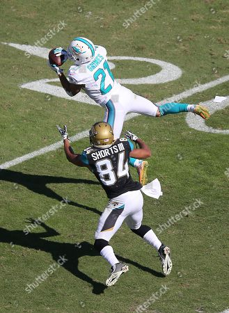 Stock Photo of Miami Dolphins cornerback Brent Grimes (21) intercepts a pass in front of Jacksonville Jaguars wide receiver Cecil Shorts (84) and returns it for a 22-yard touchdown during the second half of an NFL football game in Jacksonville, Fla