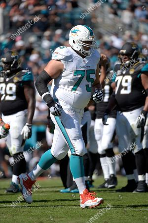 Miami Dolphins guard Nate Garner (75) runs off the field after sustaining an injury during the first half of an NFL football game against the Jacksonville Jaguars in Jacksonville, Fla