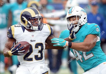 Benny Cunningham, Spencer Paysinger. Los Angeles Rams running back Benny Cunningham (23) tries to avoid the tackle by Miami Dolphins linebacker Spencer Paysinger (42) in the second quarter of a game played at Los Angeles Memorial Coliseum in Los Angeles on