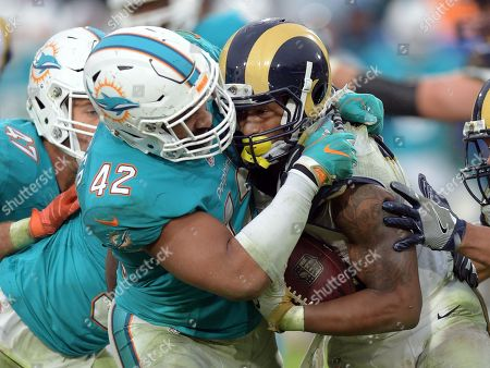 Spencer Paysinger, Tony Gurly. Miami Dolphins linebacker Spencer Paysinger (42) tackles Los Angeles Rams running back Todd Gurly (30) in the fourth quarter of a game played at Los Angeles Memorial Coliseum in Los Angeles on
