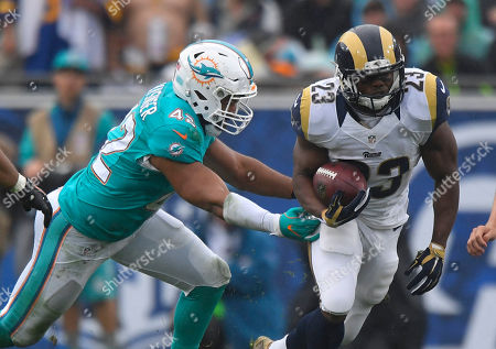 Los Angeles Rams running back Benny Cunningham runs past Miami Dolphins linebacker Spencer Paysinger during the the first half of an NFL football game, in Los Angeles