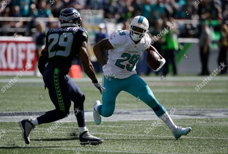 Miami Dolphins running back Arian Foster right, runs against Seattle Seahawks free safety Earl Thomas, left, in the first half of an NFL football game, in Seattle
