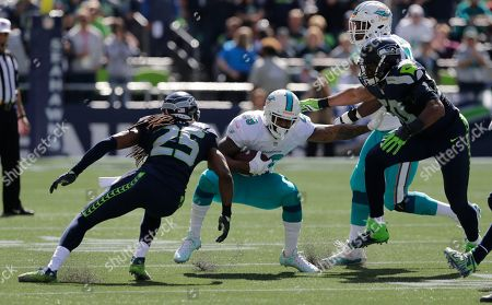 Miami Dolphins running back Arian Foster, center, runs against Seattle Seahawks cornerback Richard Sherman (25) and outside linebacker K.J. Wright, right, in the first half of an NFL football game, in Seattle