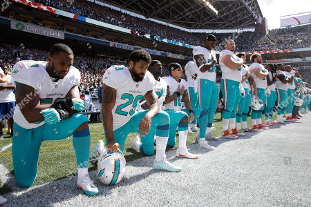 From left, Miami Dolphins' Jelani Jenkins, Arian Foster, Michael Thomas, and Kenny Stills, kneel during the singing of the national anthem before an NFL football game against the Seattle Seahawks, in Seattle
