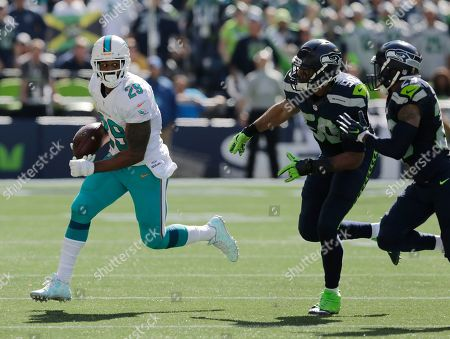 Miami Dolphins running back Arian Foster (29) runs the ball against the Seattle Seahawks in the first half of an NFL football game, in Seattle