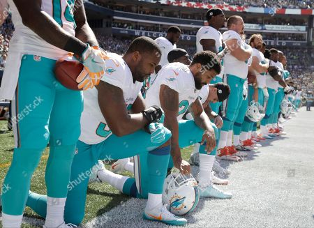 Kneeling from left, Miami Dolphins' Jelani Jenkins, Arian Foster, Michael Thomas, and Kenny Stills, kneel during the singing of the national anthem before an NFL football game against the Seattle Seahawks, in Seattle