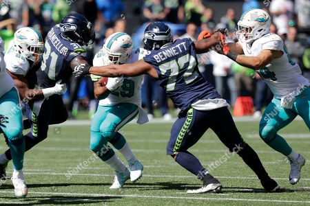 Miami Dolphins running back Arian Foster (29) tries to run between Seattle Seahawks defensive end Michael Bennett (72) and strong safety Kam Chancellor (31) in the first half of an NFL football game, in Seattle