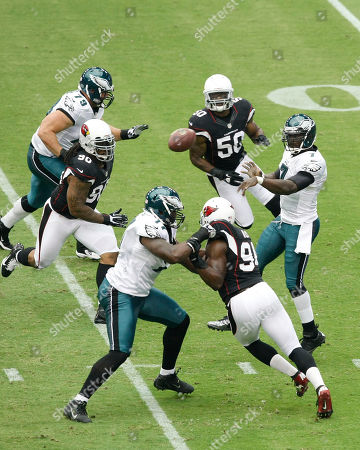 Michael Vick, Todd Herremans, Demetress Bell, Darnell Dockett, Sam Acho, O'Brien Schofield. Philadelphia Eagles' Michael Vick, far right, gets off a pass as teammates Todd Herremans (79) and Demetress Bell (77) try to block Arizona Cardinals' Darnell Dockett (90), O'Brien Schofield (50) and Sam Acho, front right, rush toward Vick during the first half in an NFL football game, in Glendale, Ariz. The Cardinals defeated the Eagles 27-6