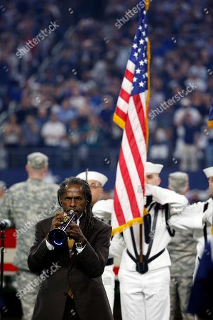 Freddie Jones plays the national anthem on the trumpet as service personnel from the Naval Air Station Fort Worth Joint Reserve Base at Carswell, Texas, display the colors before an NFL football game between the Philadelphia Eagles and Dallas Cowboys, in Arlington, Texas