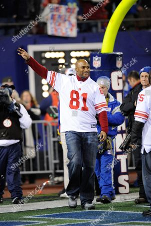 Ex-New York Giants' Amani Toomer waves before the NFL football game between the New York Giants and the Philadelphia Eagles, in New York