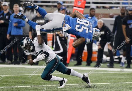 Eric Ebron, Walter Thurmond. Detroit Lions tight end Eric Ebron (85) is upended by Philadelphia Eagles strong safety Walter Thurmond (26) during the first half of an NFL football game, in Detroit