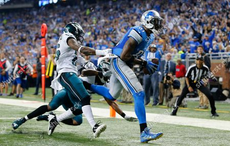 Detroit Lions wide receiver Calvin Johnson (81) drags Philadelphia Eagles strong safety Walter Thurmond, left, and cornerback Eric Rowe into the end zone for a touchdown during the first half of an NFL football game, in Detroit