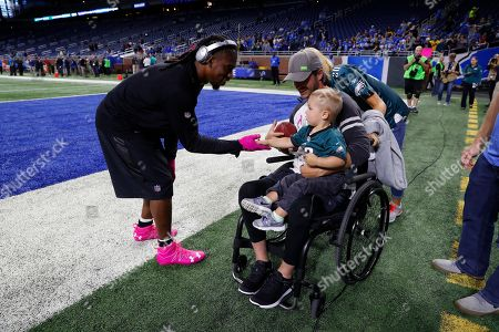 Philadelphia Eagles cornerback Ron Brooks meets with a fan during warmups before an NFL football game against the Detroit Lions, in Detroit