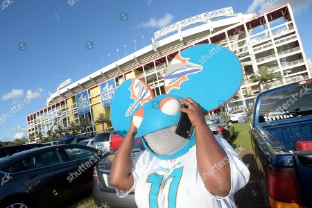 Miami Dolphins fan Shatondra Yauch wears a deadmau5 mask in the parking lot before an NFL preseason football game against the Atlanta Falcons in Orlando, Fla