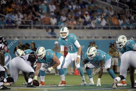 Ryan Tannehill, Anthony Steen, Laremy Tunsil, Branden Albert. Miami Dolphins quarterback Ryan Tannehill (17) stands under center Anthony Steen (65) with offensive guard Laremy Tunsil (67) and offensive tackle Branden Albert (76) at the line of scrimmage against the Atlanta Falcons during the first half of an NFL preseason football game in Orlando, Fla