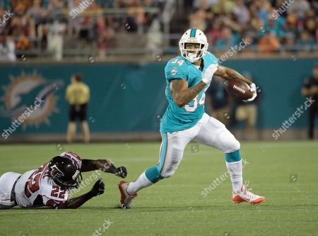Miami Dolphins running back Arian Foster (34) slips past Atlanta Falcons strong safety Keanu Neal (22) for yardage during the first half of an NFL preseason football game in Orlando, Fla