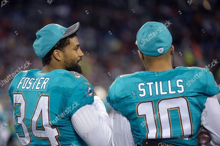 Arian Foster, Kenny Stills. Miami Dolphins running back Arian Foster (34) and wide receiver Kenny Stills (10) watch from the sideline during the second half of an NFL preseason football game against the Atlanta Falcons in Orlando, Fla., . The Dolphins won 17-6