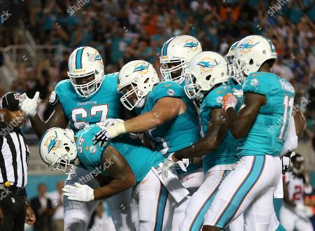 Miami Dolphins running back Arian Foster, lower left, celebrates his touchdown run with teammates during the first half of an NFL preseason football game against the Atlanta Falcons in Orlando, Fla