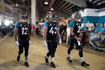Kerry Taylor, Deion Belue, Ricky Stanzi. Jacksonville Jaguars wide receiver Kerry Taylor (13), cornerback Deion Belue (43) and quarterback Ricky Stanzi (2) walk under the stands during player introductions prior to an NFL preseason football game against the Atlanta Falcons in Jacksonville, Fla