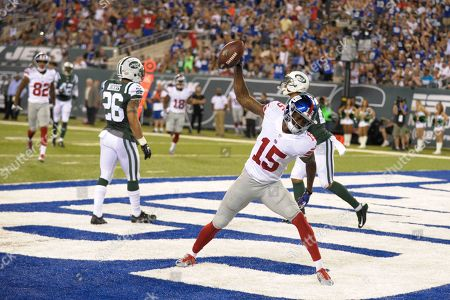 New York Giants wide receiver Tavarres King (15) spikes the ball in front of New York Jets' Darryl Morris (26) and Dee Milliner (27) after scoring a touchdown during the second half of an NFL preseason football game, in East Rutherford, N.J