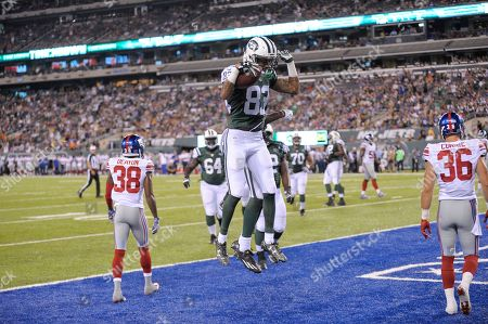 New York Jets wide receiver Robby Anderson (83) celebrates with teammates after scoring a touchdown during the second half of an NFL preseason football game as New York Giants defensive back Donte Deayon (38) and Justin Currie (36) walk away, in East Rutherford, N.J