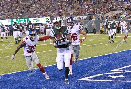 New York Jets wide receiver Robby Anderson (83) catches a pass in front of New York Giants' Donte Deayon (38) and Justin Currie (36) for a touchdown during the second half of an NFL preseason football game, in East Rutherford, N.J