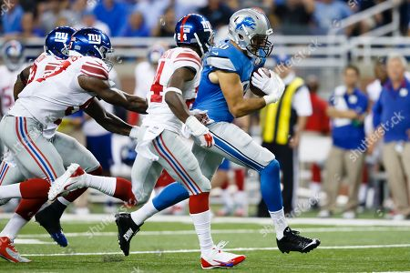 Detroit Lions tight end Joseph Fauria (80) runs the ball after making a reception against the New York Giants during an NFL football game at Ford Field in Detroit