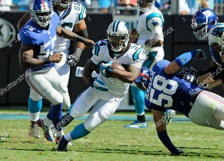DeAngelo Williams, Mark Herzlich, Keith Rivers. Carolina Panthers' DeAngelo Williams, center, runs past New York Giants' Mark Herzlich, right, and Keith Rivers, left, during the second half of an NFL football game in Charlotte, N.C