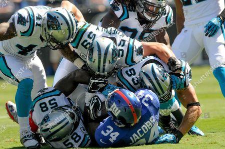 Brandon Jacobs, Thomas Davis, Captain Munnerlyn, Luke Kuechly, Chase Blackburn. New York Giants running back Brandon Jacobs (34) is tackled by the Carolina Panthers defense during an NFL football game against the New York Giants in Charlotte, NC