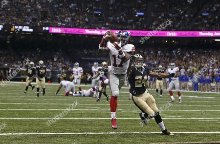 New York Giants wide receiver Dwayne Harris (17) pulls in a touchdown reception in front of New Orleans Saints defensive back Kyle Wilson (24) in the second half of an NFL football game against the New Orleans Saints in New Orleans