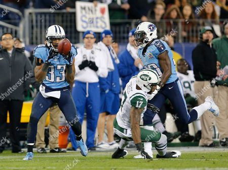 Tennessee Titans safety Michael Griffin (33) intercepts a pass intended for New York Jets wide receiver Braylon Edwards (17) in the fourth quarter of an NFL football game, in Nashville, Tenn. The Titans won 14-10. At right is Titans cornerback Jason McCourty (30
