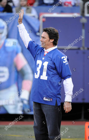 New York Giants former player Jason Sehorn gestures to the crowd during a half-time ceremony of an NFL football game between the New York Giants and the Carolina Panthers in East Rutherford, N.J