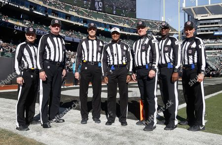 NFL side judge Walt Coleman IV (87), from left, poses for photos with head linesman Ed Camp (134), line judge Dana McKenzie (8), referee Jerome Boger (23), umpire Rich Hall (49), field judge Eugene Hall (103) and back judge Tony Steratore (112) before an NFL football game between the Oakland Raiders and the Carolina Panthers in Oakland, Calif