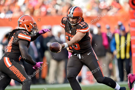Cleveland Browns quarterback Charlie Whitehurst (15) hands off to running back Isaiah Crowell in the second half of an NFL football game against the New England Patriots, in Cleveland