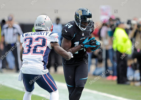 Justin Blackmon, Devin McCourty. Jacksonville Jaguars wide receiver Justin Blackmon (14) catches a pass in the endzone in front of New England Patriots free safety Devin McCourty (32) for a touchdown during the first half of an NFL football game, in Jacksonville, Fla