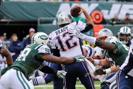 New England Patriots quarterback Tom Brady (12) is sacked by New York Jets outside linebacker Quinton Coples (98) and Muhammad Wilkerson (96) during the first half of an NFL football game, in East Rutherford, N.J