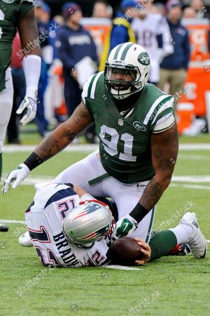 Stock Photo of New York Jets defensive end Sheldon Richardson (91) kneels over New England Patriots quarterback Tom Brady (12) after Brady was sacked by Muhammad Wilkerson and Quinton Coples during the first half of an NFL football game, in East Rutherford, N.J
