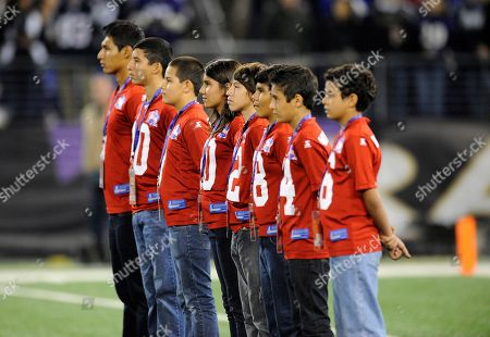 Children take part in a rendition of the national anthem by Javier Colon, not pictured, as part of the NFL's Hispanic Heritage Month before an NFL football game between the Baltimore Ravens and the New England Patriots in Baltimore