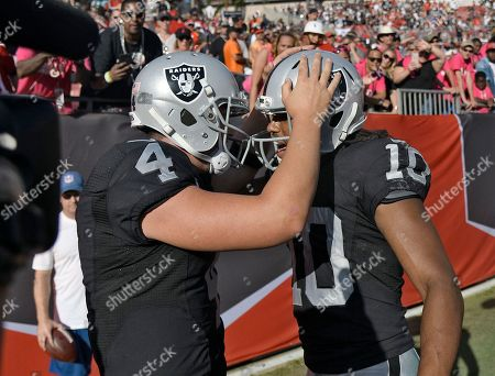 Oakland Raiders quarterback Derek Carr (4) celebrates with wide receiver Seth Roberts (10) after Roberts caught the game-winning 41-yard touchdown pass against the Tampa Bay Buccaneers during overtime in an NFL football game, in Tampa, Fla