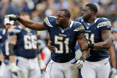 Takeo Spikes, Randy McMichael. San Diego Chargers inside linebacker Takeo Spikes (51) yells as he is held back by tight end Randy McMichael after Spikes was ejected from the NFL football game along with Oakland Raiders running back Mike Goodson, during the first half, in San Diego